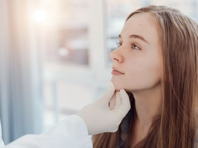 Experienced pediatrician examining patient face in the hospital