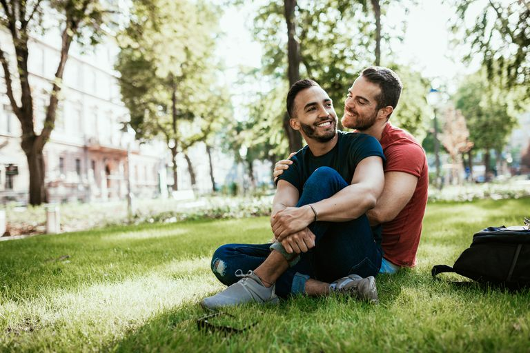 Gay couple - Latino and European millennial men - enjoying in park in summer - stock photo