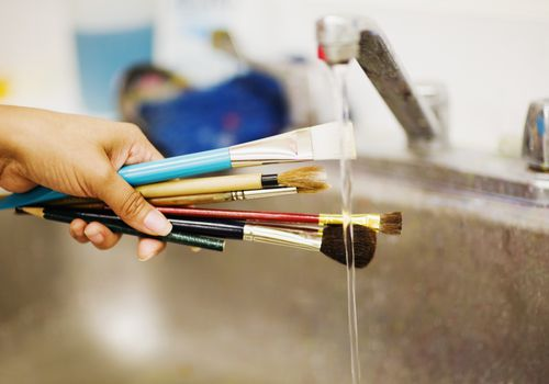 Person's hand washing paint brushes under a faucet