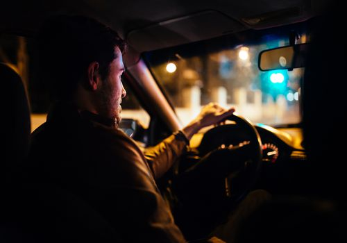 Man driving a private taxi through city streets at night