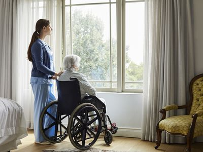 Caregiver with senior woman looking through window
