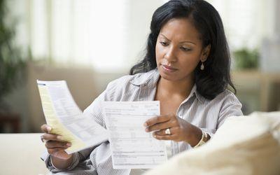 Young Hispanic woman looking at bills.