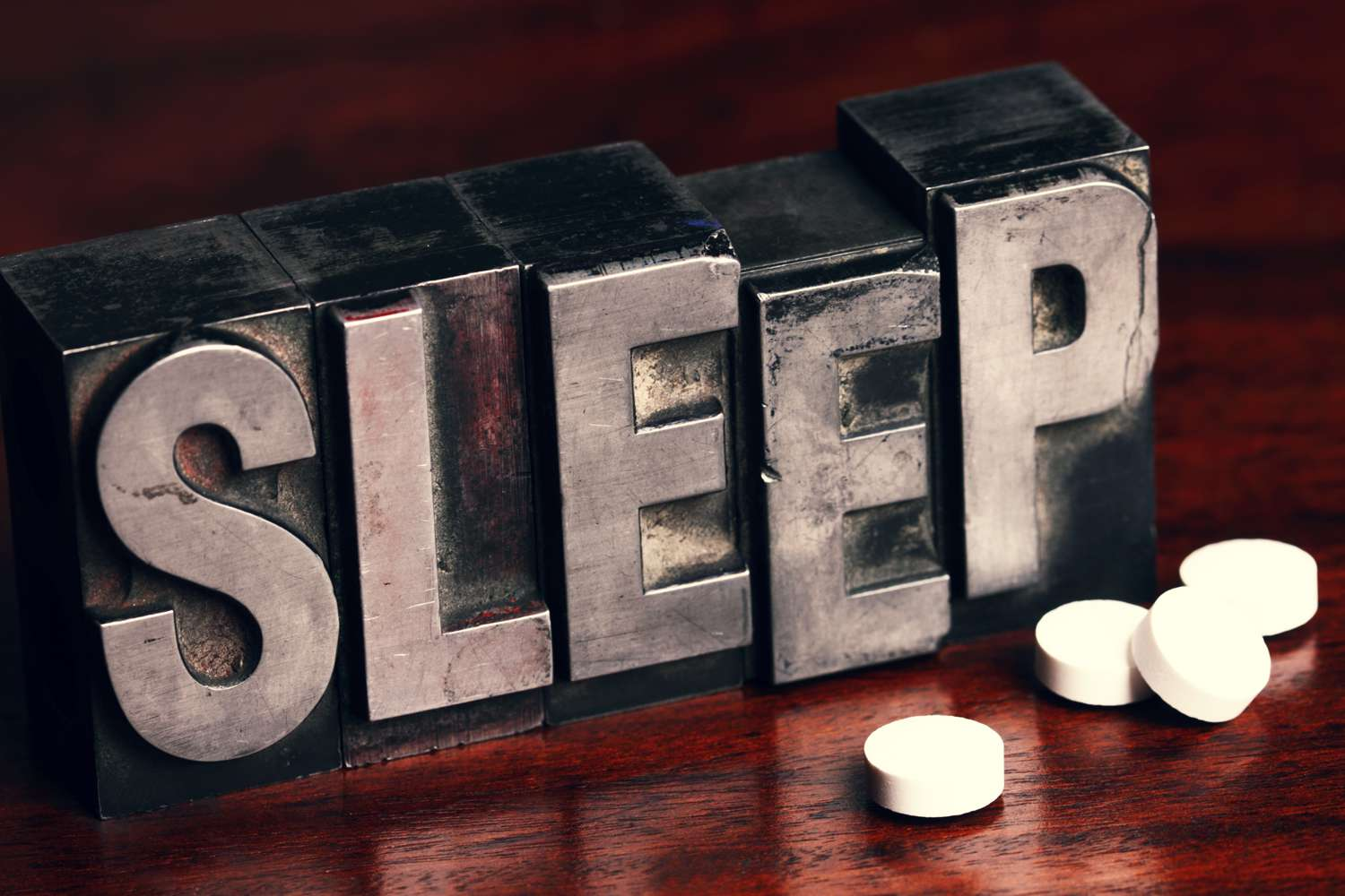"""Melatonin supplement pills in front of typesetting letters that spell out """"sleep"""""""