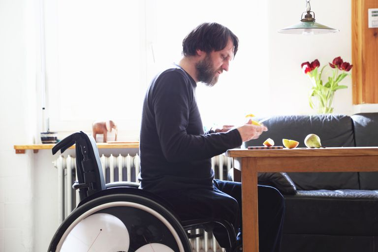 Man in wheelchair cutting fruit