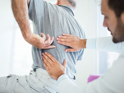 Doctor evaluating pain in man's back