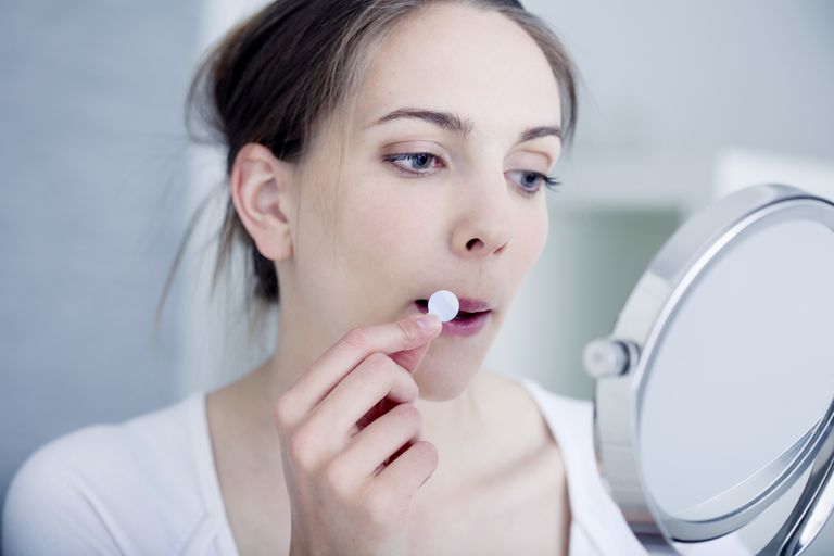 Woman applying a patch to treat labial herpes.
