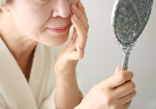 Senior woman checking herself with a hand mirror