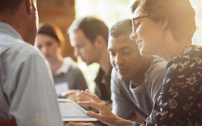 Business people sharing digital tablet in meeting