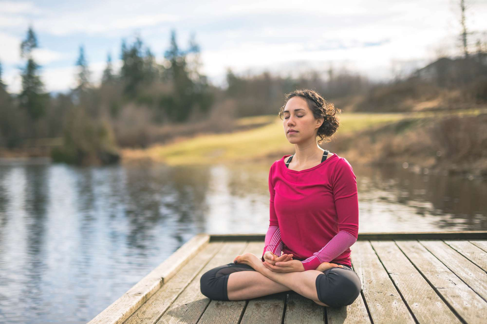 Woman practicing yoga on a dock