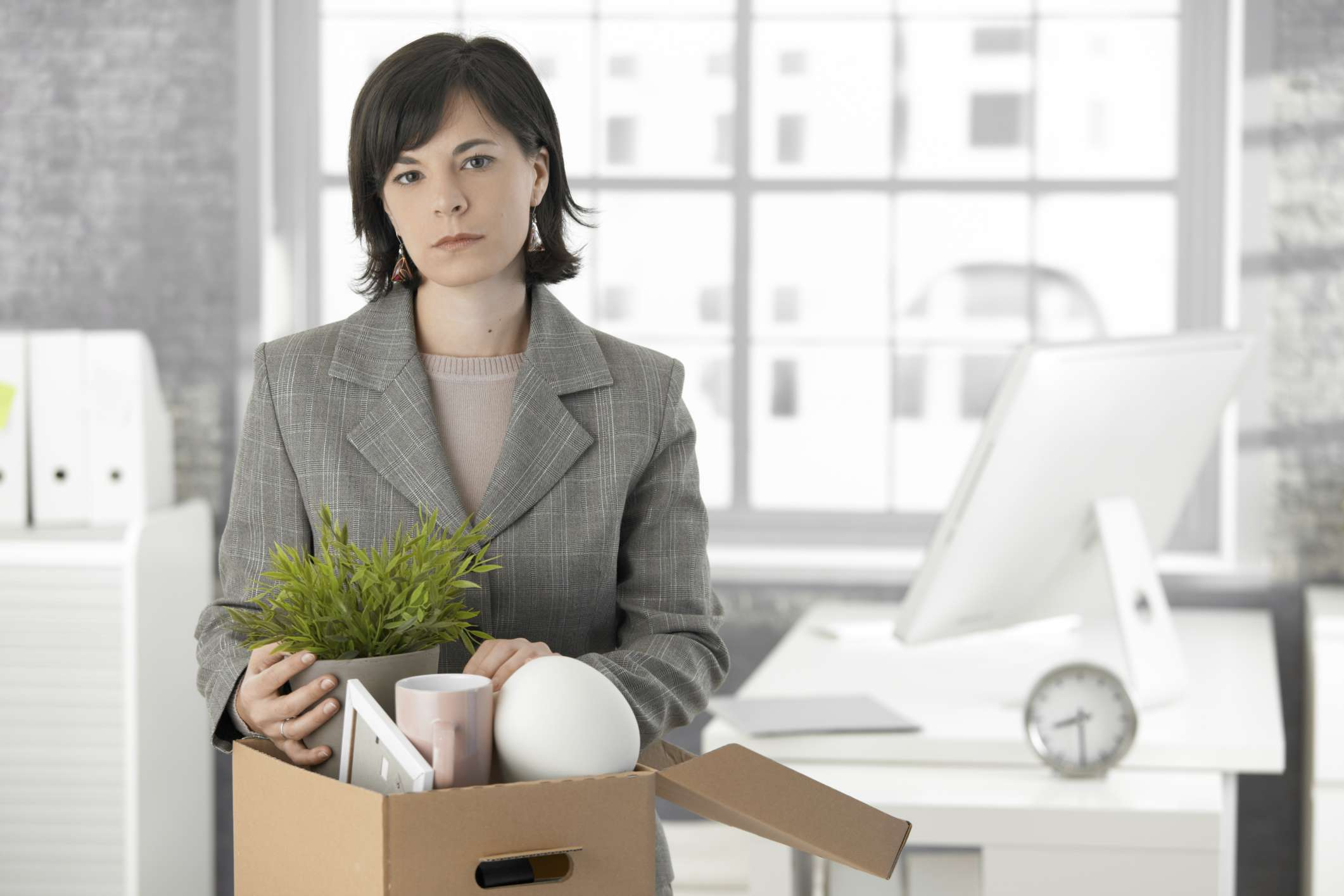 Woman packing up her belongings in an office after being fired