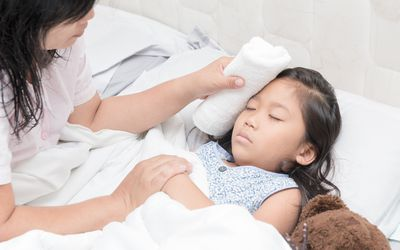 mother using cloth to wipe feverish daughter's forehead