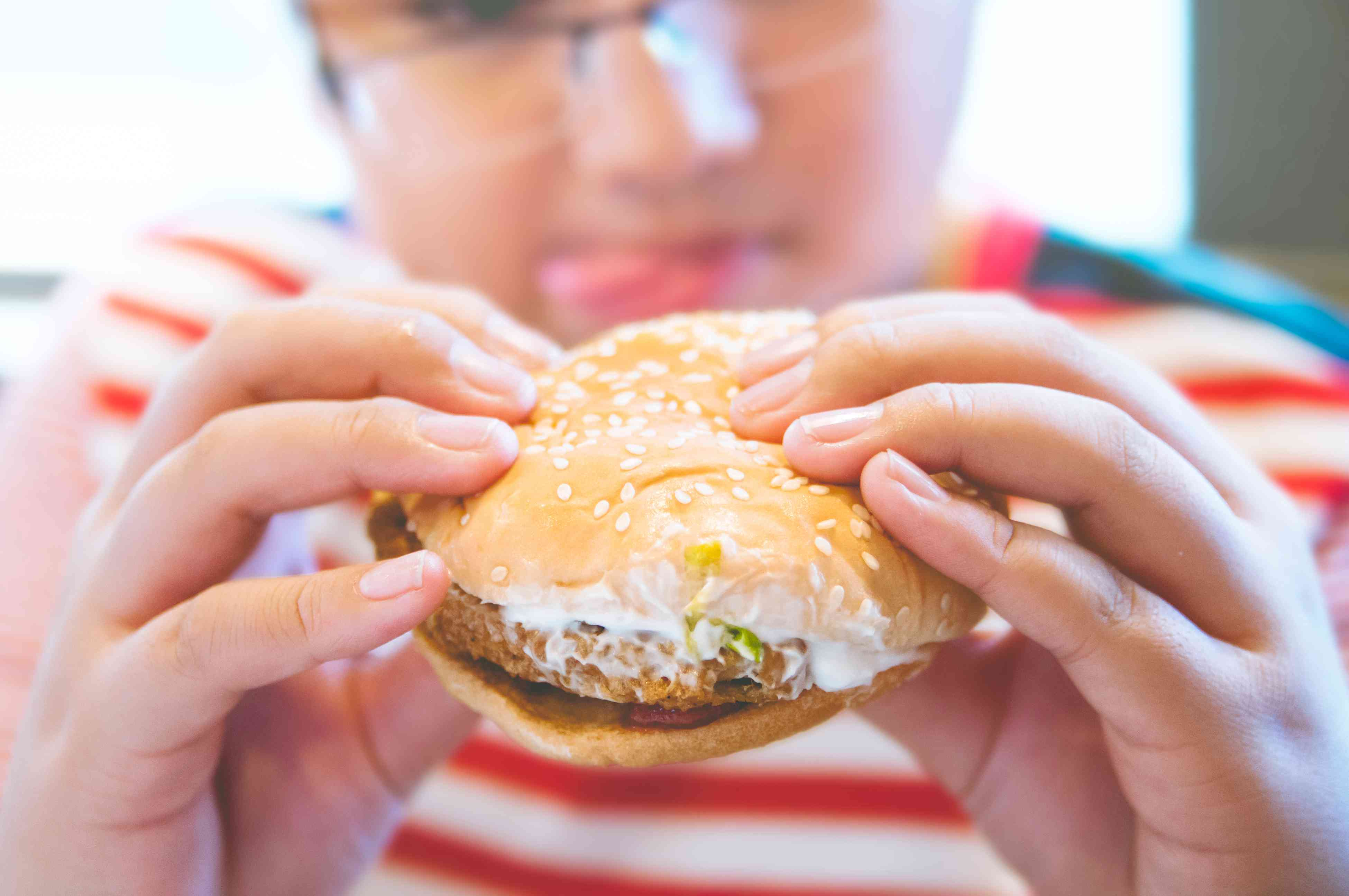 Young man in a striped shirt eating hamburger, focus on the burger