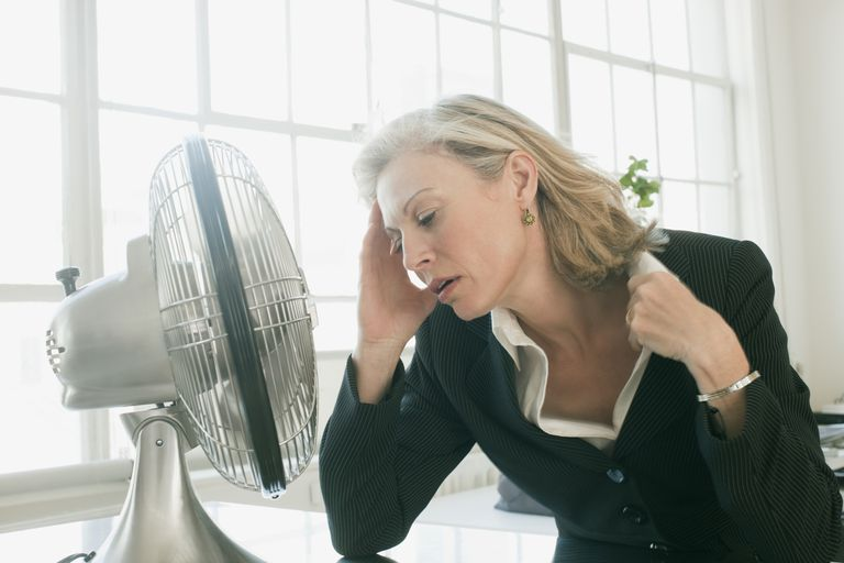 Hot businesswoman sitting in front of fan