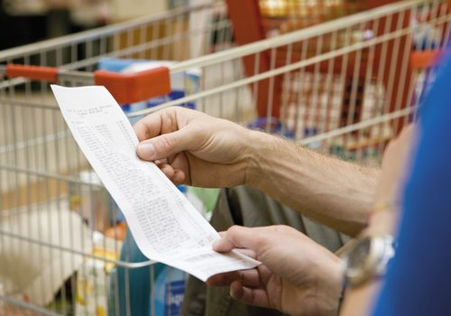 Close up of an older white person's hands holding a grocery receipt with a grocery cart in the background.