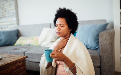 woman touching sore throat