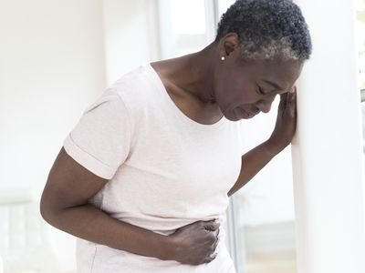 A mature woman of African descent holding her stomach in discomfort.