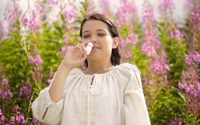 A woman outside using allergy nasal spray