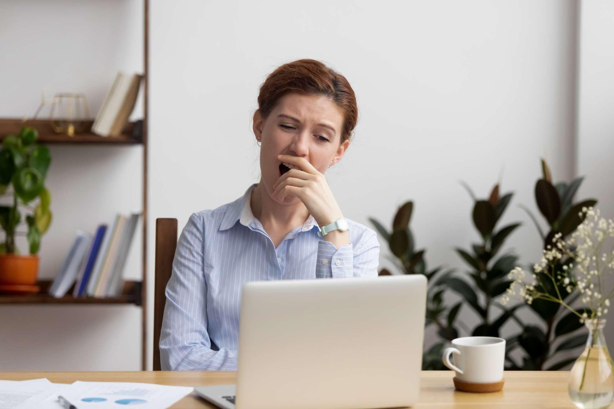 Woman yawning looking at computer