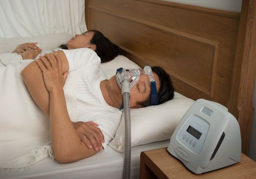 Man Wearing CPAP Mask in bed with woman next to him