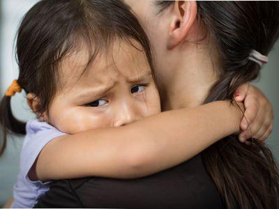 sad girl in mom's arms