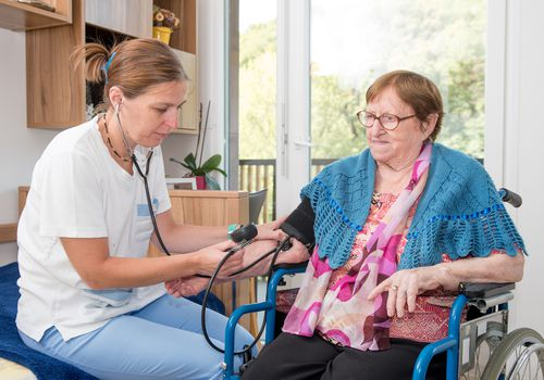 Nurse Checking Blood Pressure of Senior Female Patient