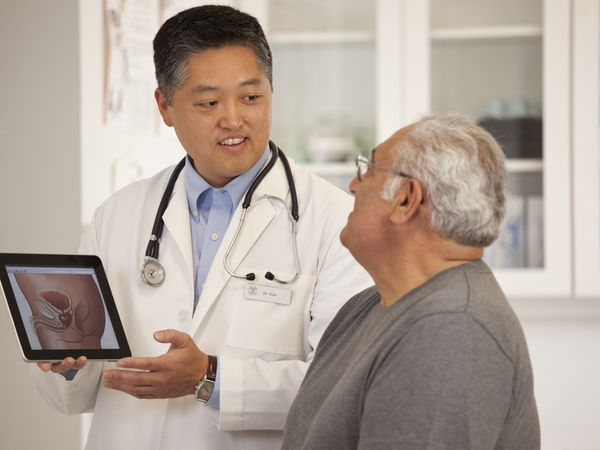 Doctor using digital tablet to talk to senior man - stock photo