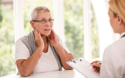 Senior woman complaining to her doctor about her tonsils