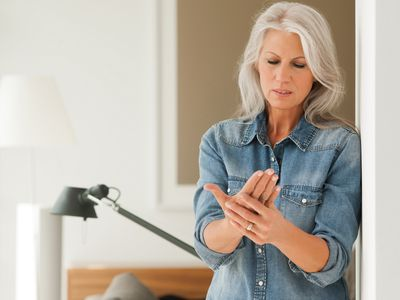 woman with white hair holding her hand in pain