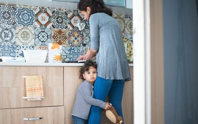 A POC woman standing at the sink with her back to the camera; a POC toddler is clutching her leg and holding a teddy bear.