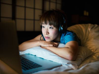 Woman using computer in dark room