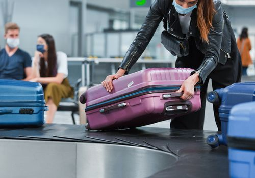 Traveler wearing face mask getting their luggage.