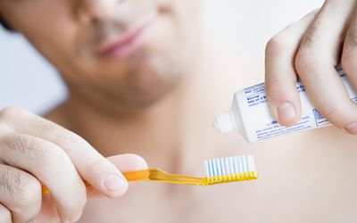 A man putting toothpaste on his toothbrush