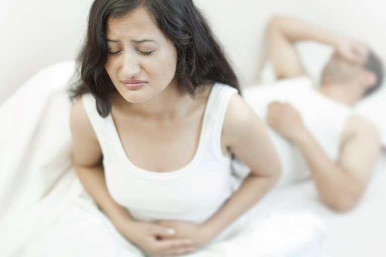 Grimacing woman holding her aching stomach
