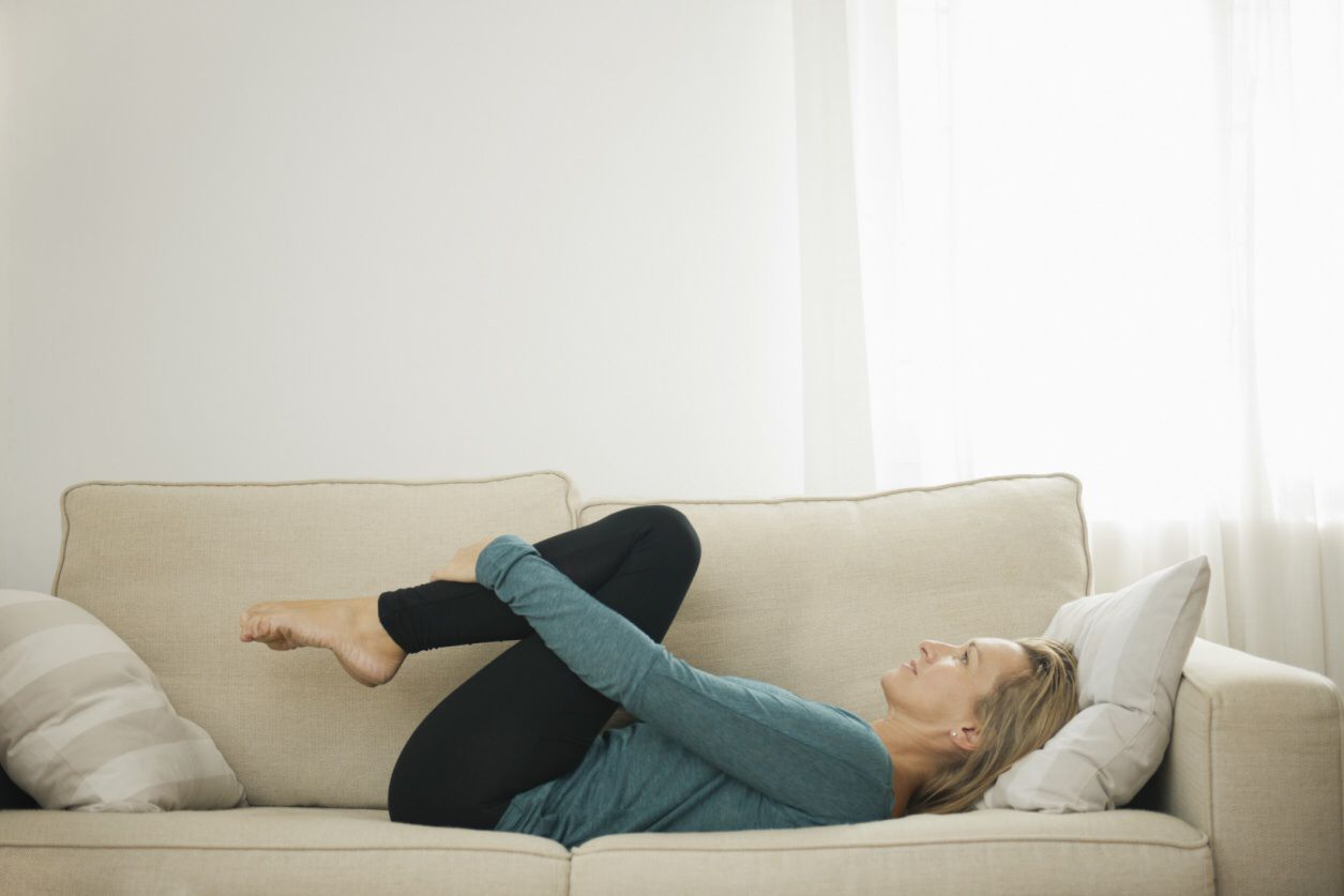 Woman stretching her back on the couch.