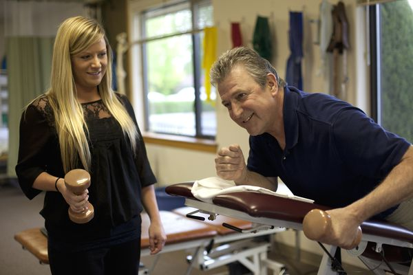 Physical therapist helping patient strengthen arms
