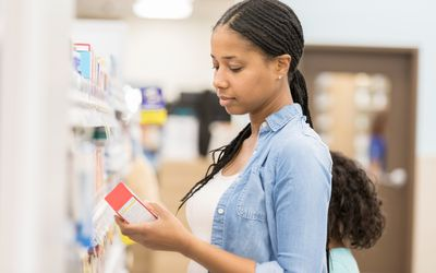 woman looking at medication in store aisle