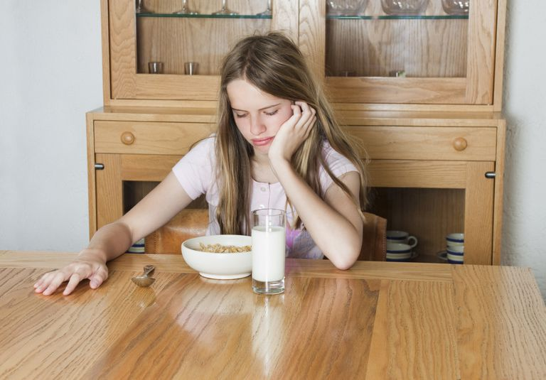 tween girl grimacing at bowl of cereal
