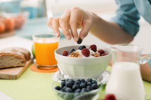 Woman having an healthy delicious breakfast at home with yogurt, cereals and fresh fruit, she is picking a blueberry