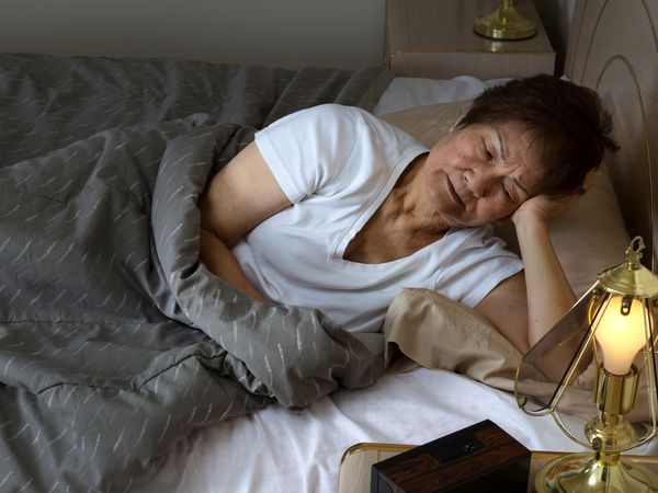 An elderly woman lays in bed, resting half-supported by one arm. She is still awake.