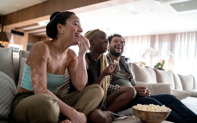 Friends together watching tv at home - stock photo