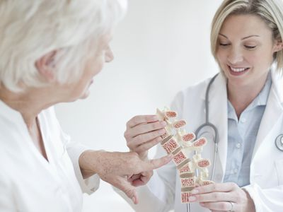 Doctor looking a spine figure with her patient