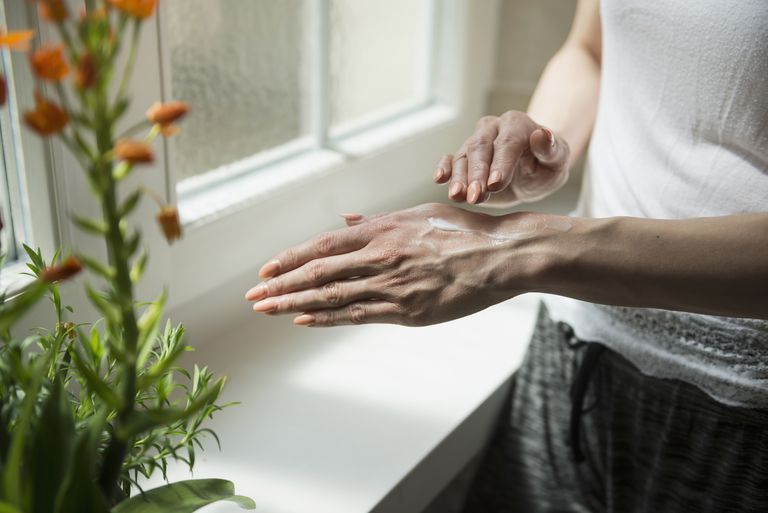 Woman applying topical cream to her hands.