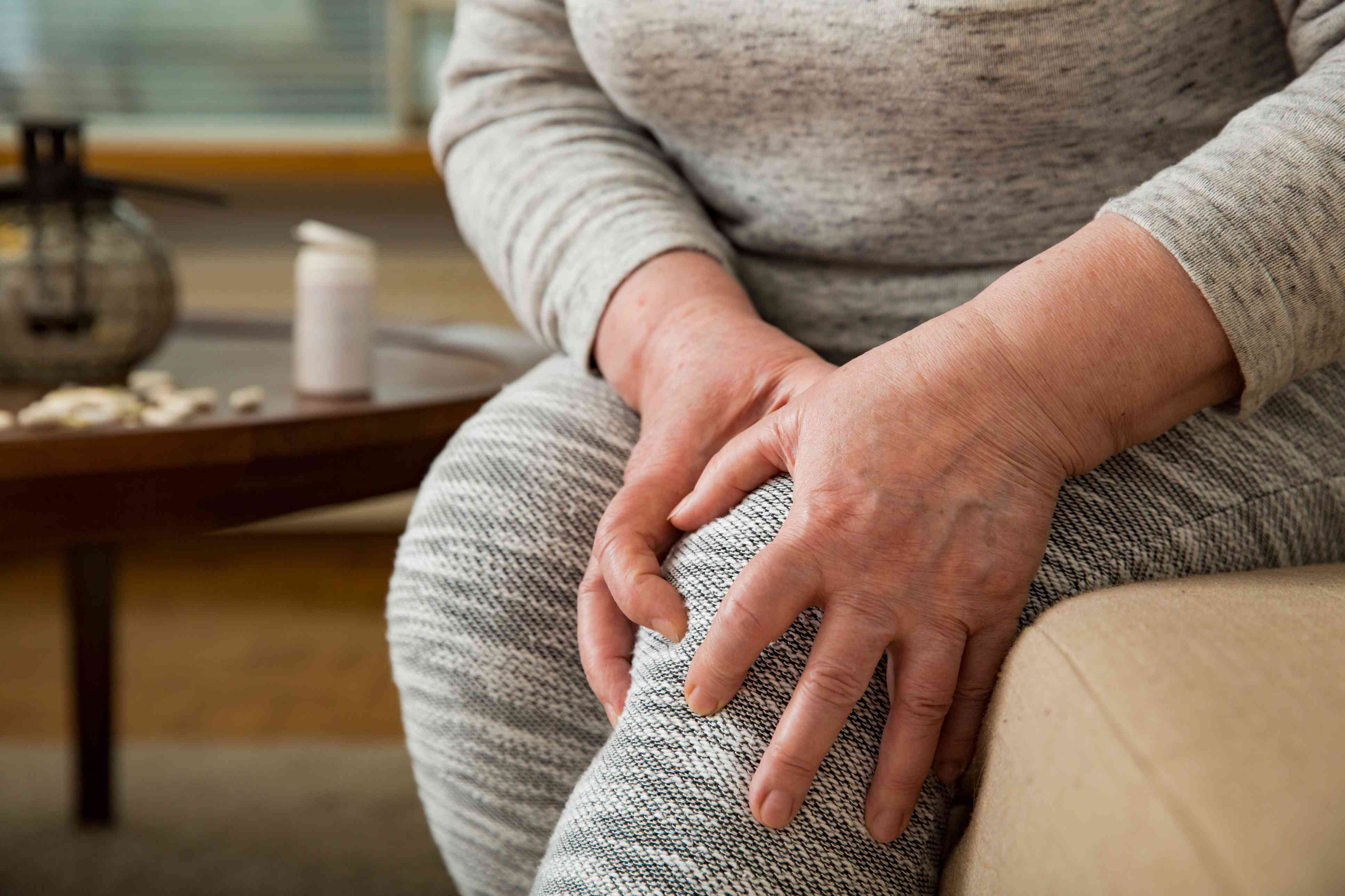 Older woman suffering from pain in knees at home. Holding her knee and massaging with hands, feeling exhausted, sitting on sofa in living room. Close-up. Medications and pills on table