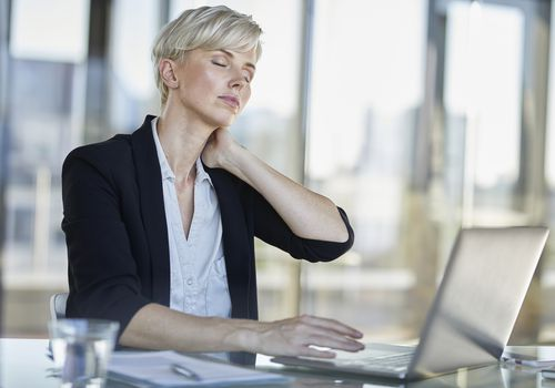 woman sitting her desk and rubbing her neck