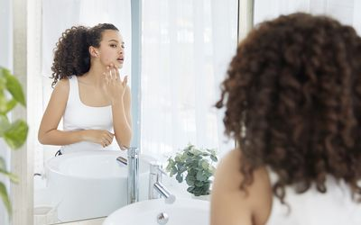 Person touching her face and sees a pimple looking in the mirror in bathroom - Stock Photo