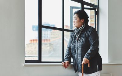 An older adult woman with a cane standing by a window looking outside.