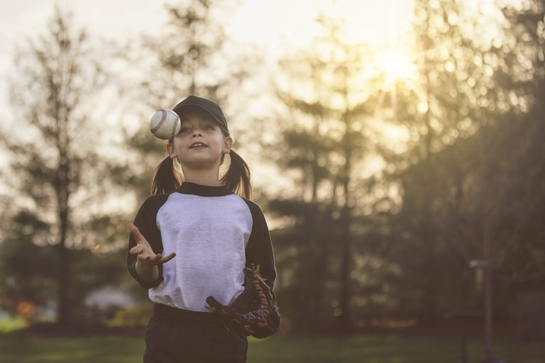 Little girl throwing a baseball into the air