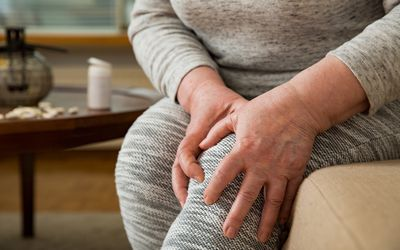 Senior woman suffering from pain in knees at home. Holding her knee and massaging with hands, feeling exhausted, sitting on sofa in living room. Close-up. Medications and pills on table