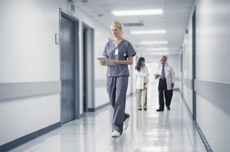 Caucasian nurse reading medical chart in hospital