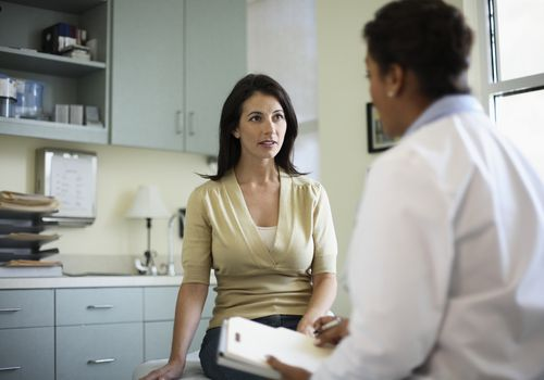 Woman speaking with a female doctor in the office